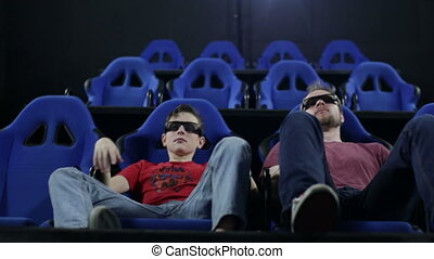 Father and son in a 5d cinema watching a movie - People in...