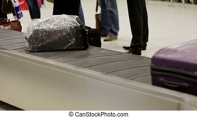 People are waiting for luggage at the airport. Baggage...