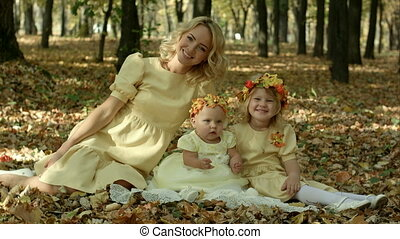 Young mother with maple leaves sitting with children