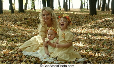 Beautiful young woman with maple leaves sitting with her baby