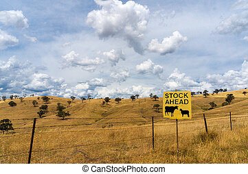 Australian outback with Stock Ahead road sign