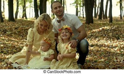 happy young family with their children spending time outdoor in the autumn park
