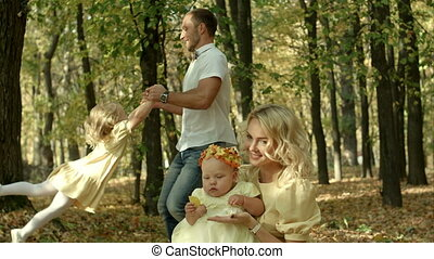 Father spinning his daughter in the autumn forest