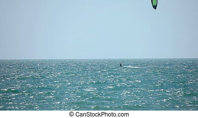 Kite surfer in ocean - Kitesurfer surfing on the waves with...