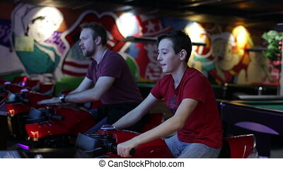Teen and man ride on motorbike simulation game - Slot...