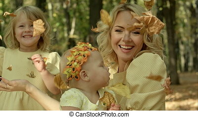 Young happy mother and her children with maple in autumn...