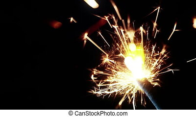 sparkler fireworks burning on a black background,...