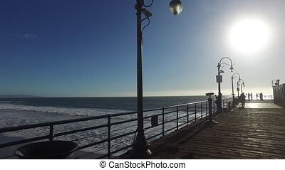 ocean sparkles and moves from beyond the boardwalk - The...