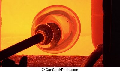 Glass-blower working - the molten glass is picked with the...