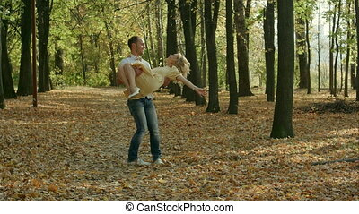 Young man spinning his girl in a circle in autumn park