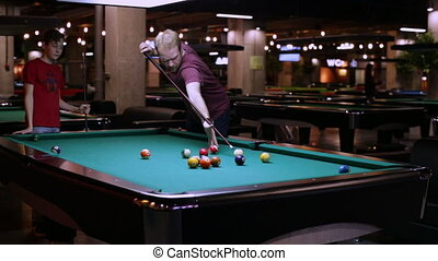 Friends playing in pocket billiards - Man and teen playing...