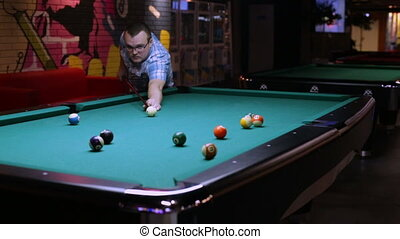 Young man playing in pocket billiards - Young man playing...