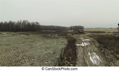 Aerial view of dirty road at farm in country side, russia...