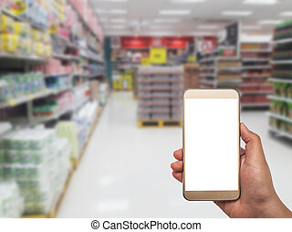 Hand with smartphone on blurred in department store - Hand...