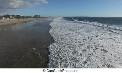 Foamy waves gently lap at the shoreline - SANTA MONICA, CA...
