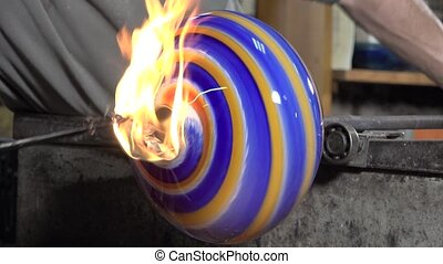 Glass-blower working - shaping the soft glass with pliers