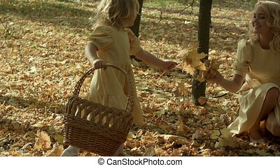 Mother and daughter play in autumn park. Parent and child walk in the forest on a sunny fall day. Children playing outdoors with yellow maple leaf.