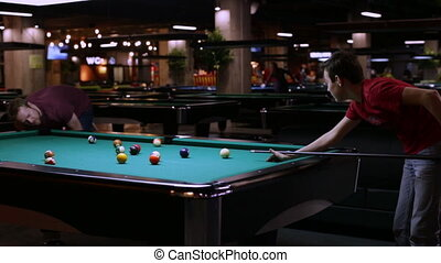 People playing in pocket billiards - Man and teen playing...