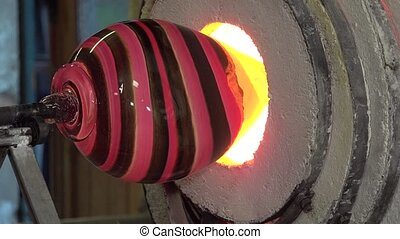 Glass-blower working - the object is reheated before...