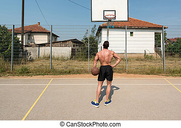 Basketball Player Shooting In A Playground - Basketball...