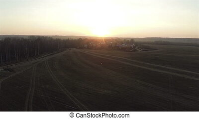 Aerial view of field roads at sunset near village in the...