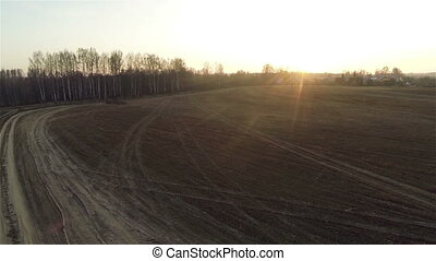 Aerial view of field roads at sunset near village, autumn...