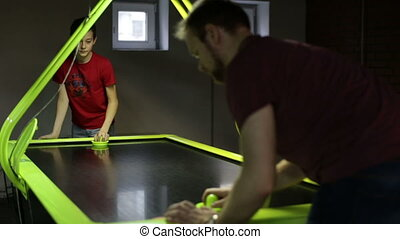 Teen with man playing air hockey game - Young man and teen...