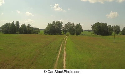 Aerial view of road in green red field, sunny day in country...