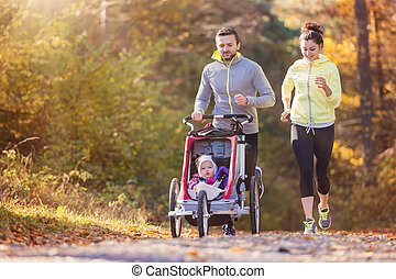 Young family running - Beautiful young family with baby in...