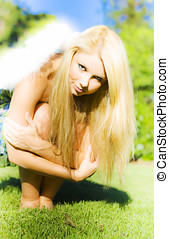 Fallen Angel - Pretty young blonde woman with feathery angel...