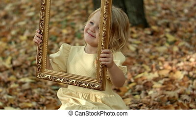 Girl posing with picture in autumn park Shot on BMCC RAW...