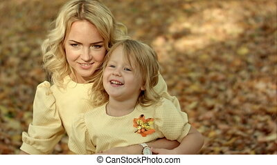 Happy mother with her daughter in autumn park