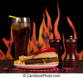 Fast food set of a burger, french fries and cola on flames...