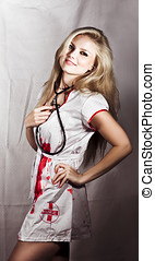 Evil Nurse Concept. Smiling pretty evil nurse wearing a...