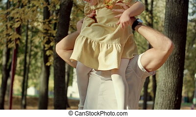 Little girl riding on dads neck at autumn park