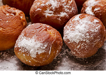 Close up on delicious doughnuts with icing sugar on wooden background.