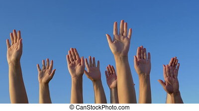 Raised hands against blue sky - Male and female hands raised...