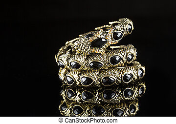 golden bracelet form of snake isolated black background -...
