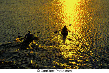 Man and Woman Kayaking at Sunset - Silhouette of Man and...