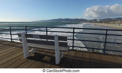 Bench on the Santa Monica pier and Pacific Ocean waves in...