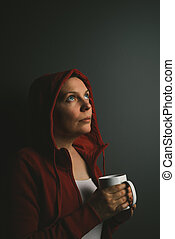 Beautiful red hooded lonely woman drinking coffee