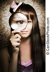 Beautiful female watching through magnifying glass -...