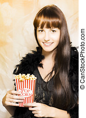 Buttered popcorn at showtime - Happy smiling young woman in...