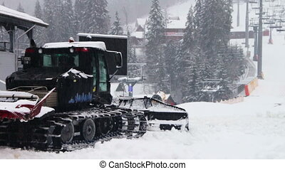 Snowcat works on a mountain slope at the ski resort -...