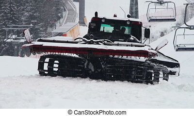 Snowcat works on a mountain slope at the ski resort.