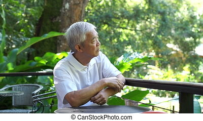 Asian senior guy thinking and worry in green lush nature...