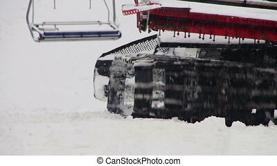 Snowcat works on a mountain slope at the ski resort. -...