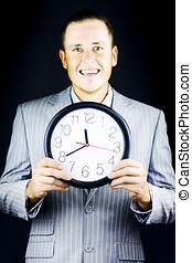 Smiling man in suit, holding a clock on black background