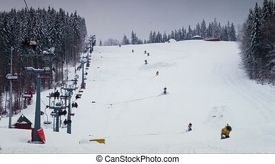 Ski lifts work on a snowy mountainside. Timelapse - People...