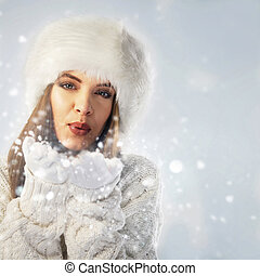 Close-up portrait of a woman blowing snow